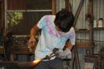 Jakob, following Buddy's instructions, forges a sliding bolt piece