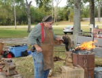 Tim using his antique forge